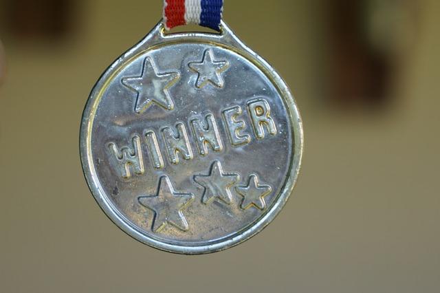 silver medal with winner written on it